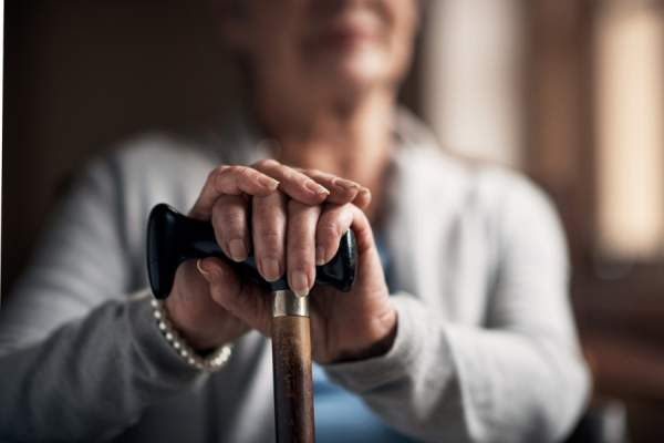 woman's hands holding cane