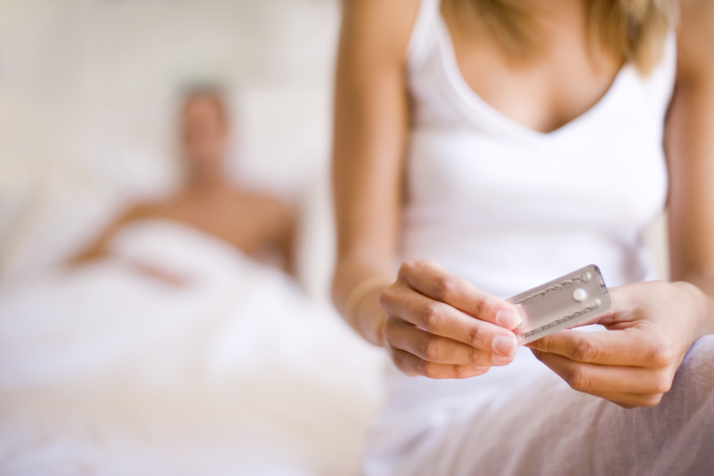 Woman taking the morning-after pill in bed, her partner is behind her