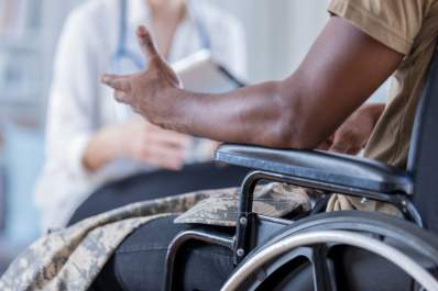 man in wheelchair gesturing towards doctor