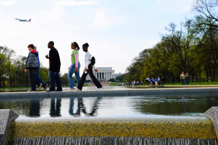 Young people walking with the Lincoln Memorial in the background