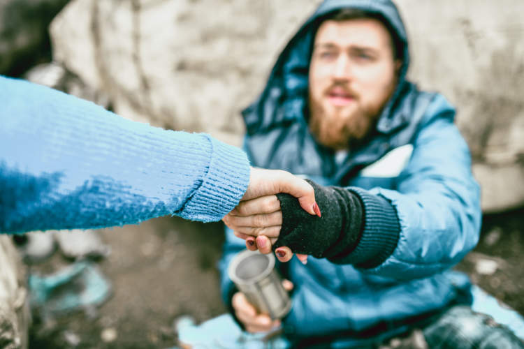 Homeless Man Shaking a Person's Hand