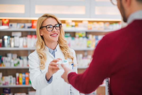 pharmacist handing man prescription