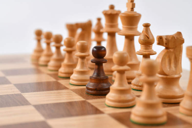 chess pieces on chessboard, one pawn is different than the rest of the pieces