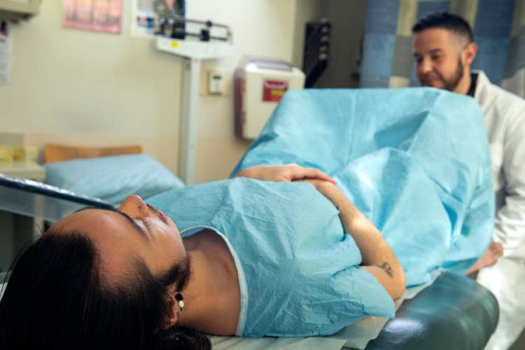 A genderqueer person in a hospital gown receiving a pelvic exam