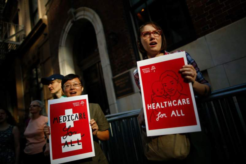 "Two activists at protest holding signs reading ""HEALTHCARE for all"" and ""MEDICARE for all"""
