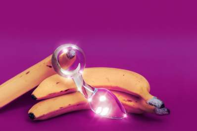 Glass anal sex toy and a yellow banana on a colored background