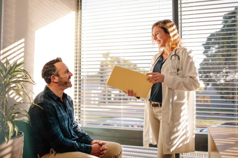 Smiling female doctor holding a medical report file and talking with male patient sitting on sofa