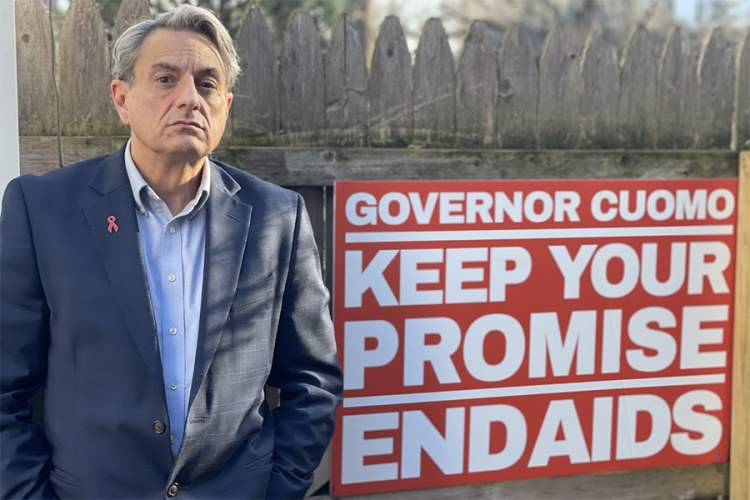 "Perry Junjulas next to a sign that says ""Governor Cuomo Keep Your Promise End AIDS'"