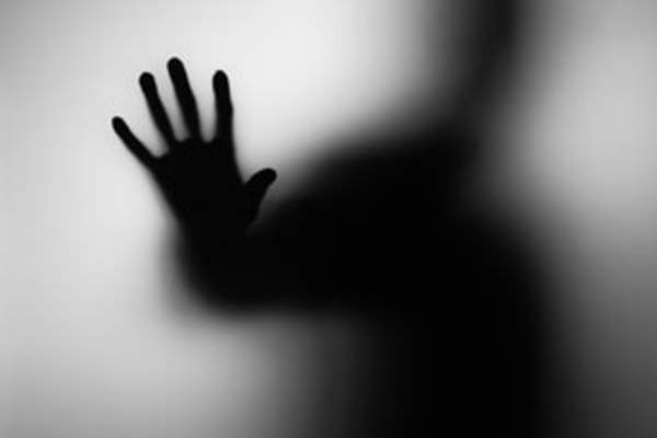 shadow/silhouette of person pressing hand against glass