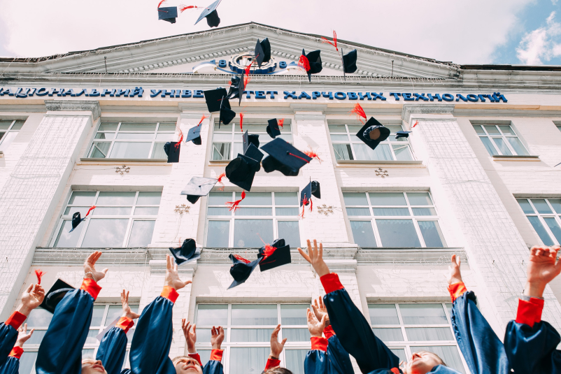 Graduates throwing graduation caps, motorboards in the air.