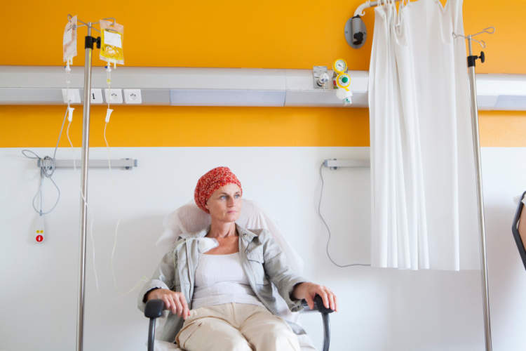 woman in headscarf receiving chemotherapy in yellow room