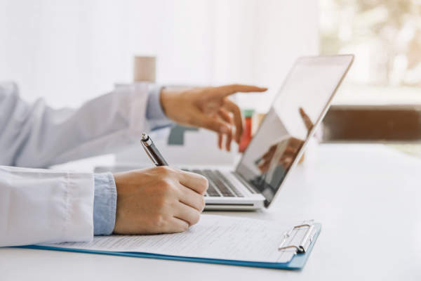 Doctor writing medical documentation and using laptop