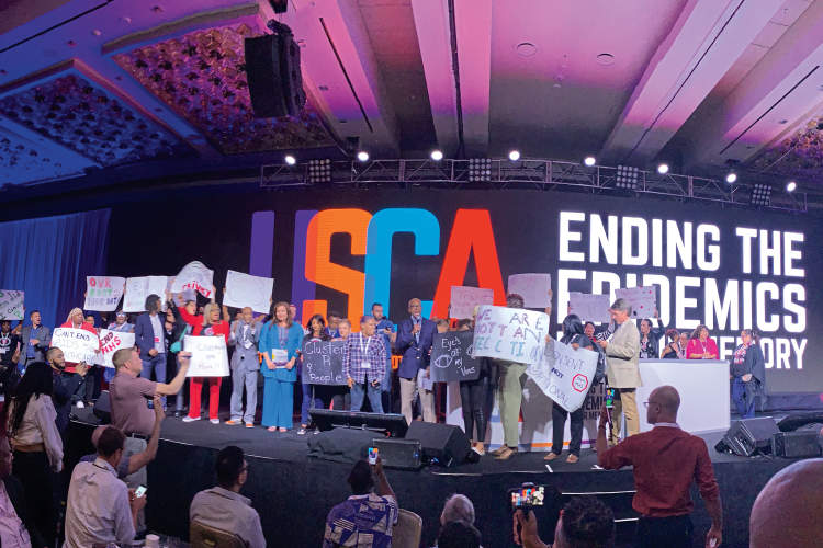 HIV community members protest the use of molecular surveillance onstage at the 2019 United States Conference on AIDS