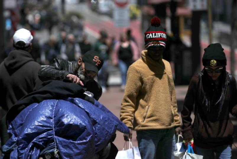 Pedestrians walk by a homeless man as he arranges his belongings on a cart on May 17, 2019 in San Francisco, California