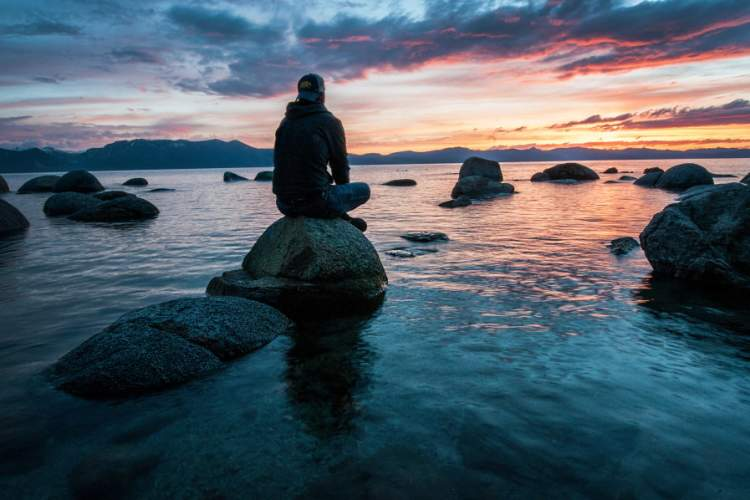 man sitting on rock in the water meditating