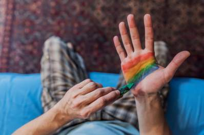 Man painting rainbow flag on his hand