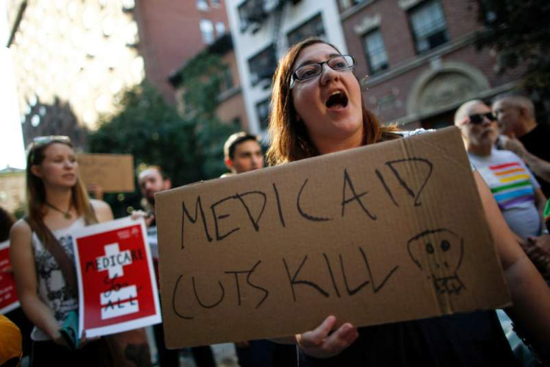 "woman at rally with sign reading ""MEDICAID CUTS KILL"""