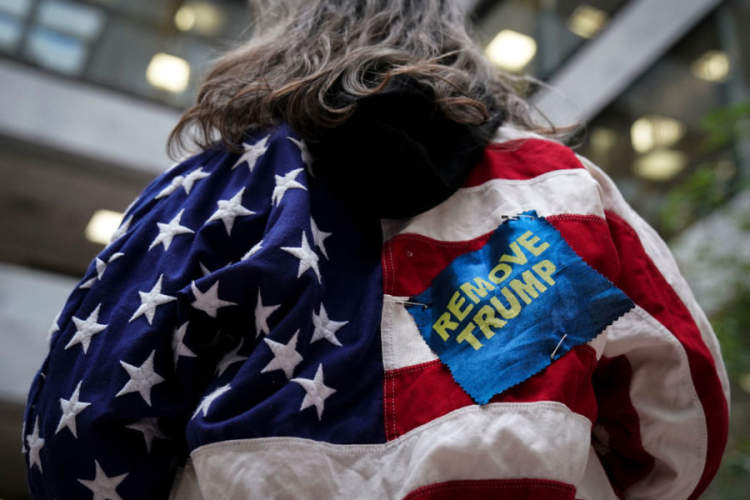 "person at political rally wearing American flag and patch that reads ""REMOVE TRUMP"""