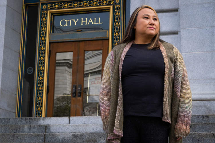 Cecilia Chung standing in front of San Francisco City Hall entrance