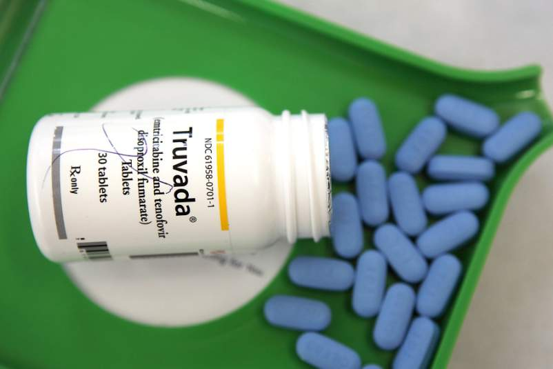 a bottle of Truvada on top of Truvada pills at pharmacy