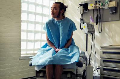 A transgender person sitting in a hospital gown sitting in an exam room