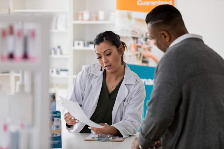 pharmacist reviews prescription with customer