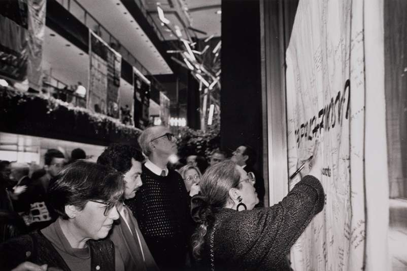 Archival photo of concertgoers writing the names of loved ones on a special panel of the AIDS Memorial Quilt in 1992