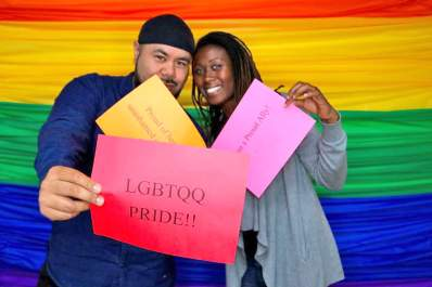 Tone Vai and Kamailia Williams of Instituto Familiar de la Raza hold LGBTQ pride signs during Give OUT Day 2017