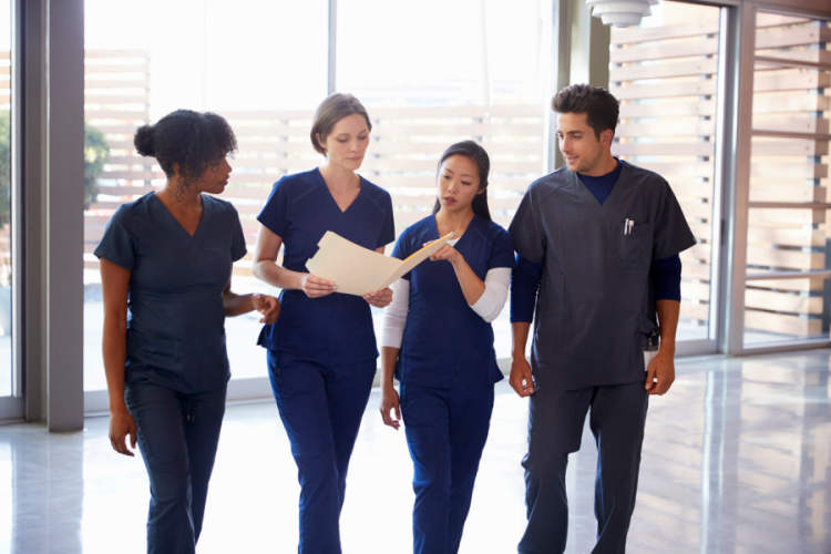 nurses walking together and looking at medical chart
