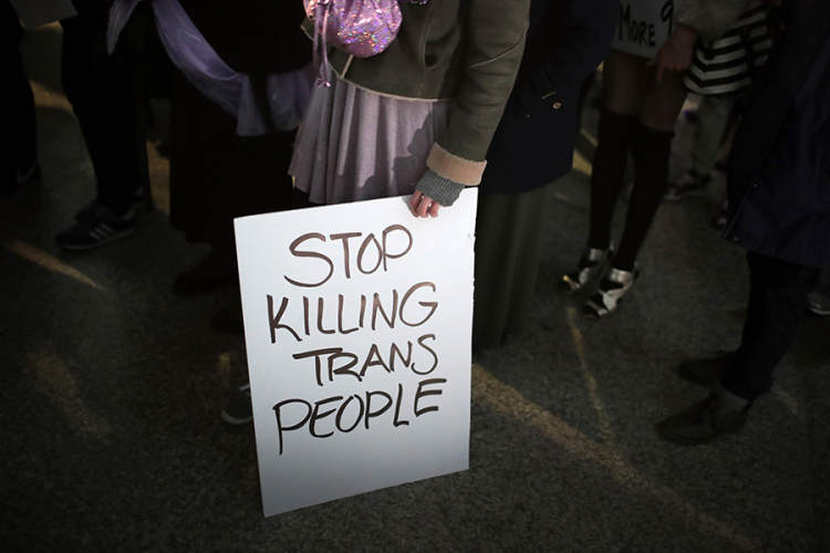"Person holding protest sign reading ""Stop killing trans people"""