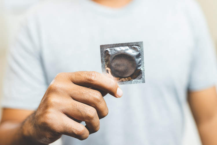 Man holding a wrapped condom.