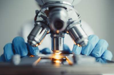 Close up of doctor examining of test sample under the microscope