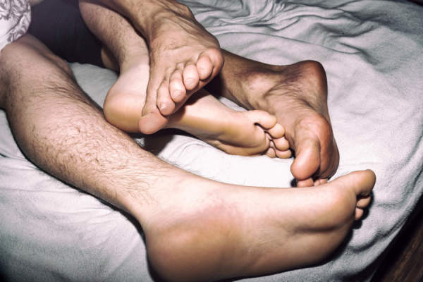 men's feet tangled in bed
