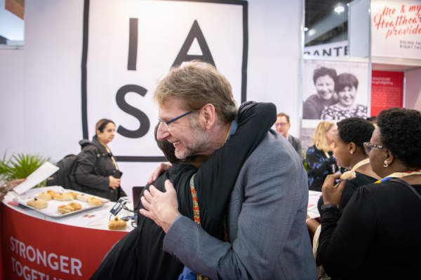 Anton Pozniak, moderator for the IAS 2019 press conference about HIV treatment research, greeting an Educational Fund Scholarship recipient at the IAS Exhibition Booth.