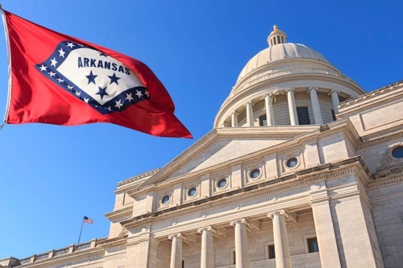 Arkansas flag flying high beside the State Capitol Building