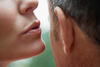 Woman whispering into man's ear