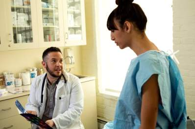A transgender woman in a hospital gown speaking to her doctor, a transgender man, in an exam room