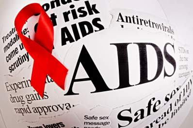 red ribbon on top of newspaper clippings about HIV/AIDS