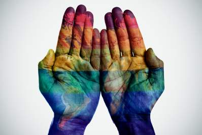 World map and rainbow flag on hands