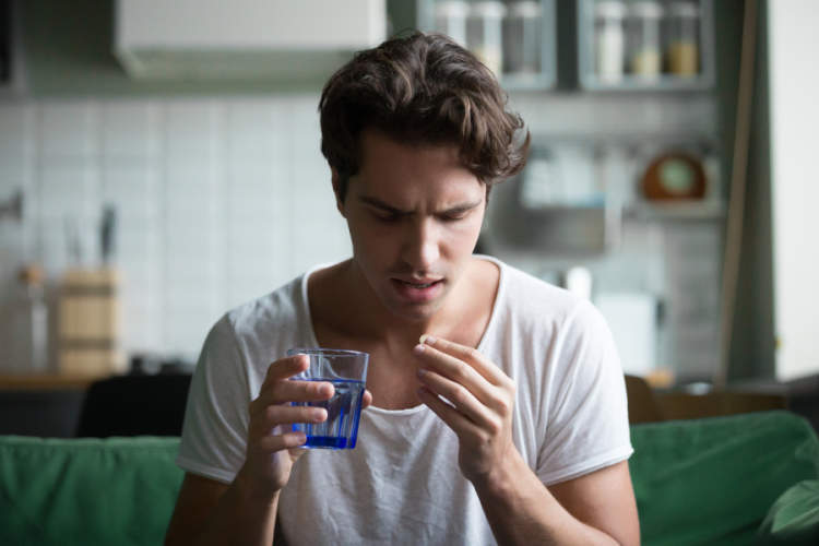 young man looking at pill before taking it