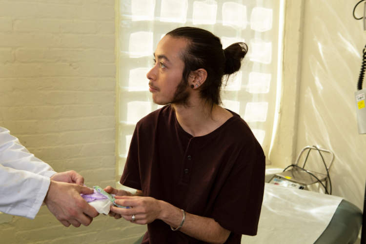 A genderqueer person receiving menstrual products from a nurse