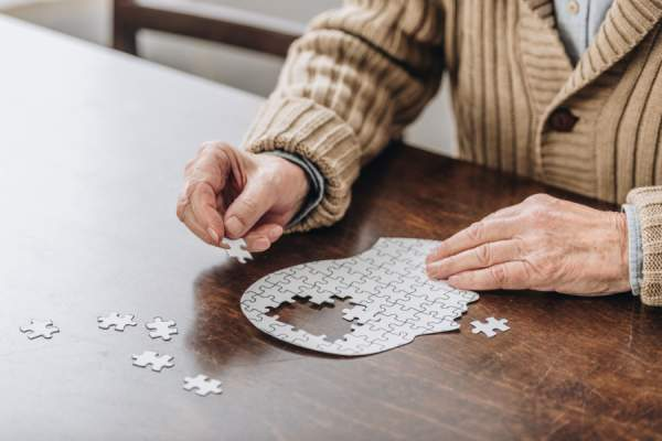 Cropped view of senior man playing with puzzle shaped like head