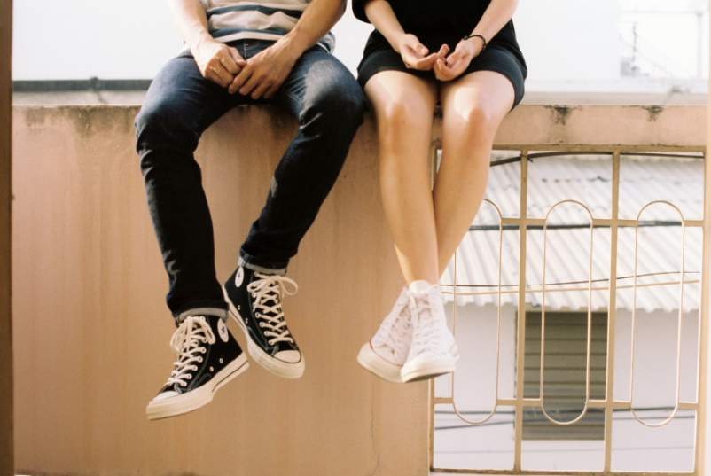 heterosexual couple sitting on ledge