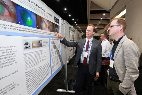 Attendees discuss a poster presentation at IDWeek 2017 (Credit: Infectious Diseases Society of America)