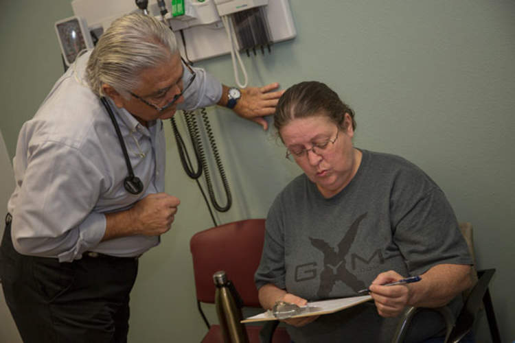 Dr. Ronald Cirillo helps Deborah Hatfield fill out paperwork at a Florida clinic before running a test to see whether she has hepatitis C
