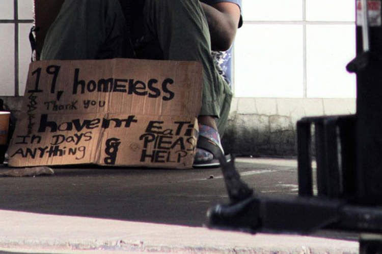 Homeless teenager with sign asking for help
