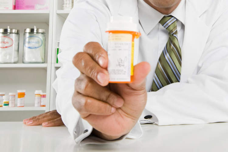 A pharmacist's hand holding a pill bottle