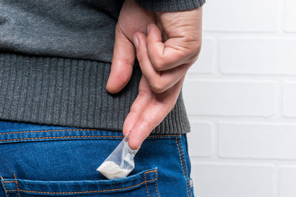 A man takes out of his jeans pocket a package of drugs