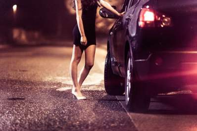 A prostitute standing outside of a car