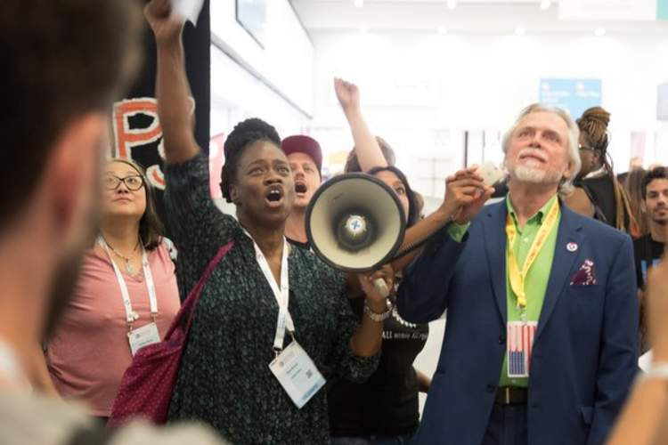 na Brown of the Southern AIDS Coalition (left) and Charles King of Housing Works protest the AIDS 2020 conference location